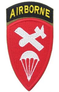Shield shaped embroidered red patch with white plan and parachute silhouette in the middle, with a black embroidered arch attached to the top with AIRBORNE in yellow