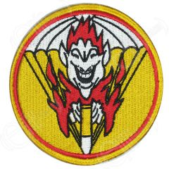 Circular embroidered yellow patch with red detail, including a white cartoon face with red hair, surrounded by red cartoon flames