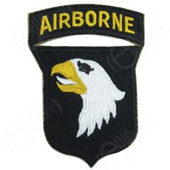 Shield shaped dark brown embroidered patch with right facing eagle face with black eye, yellow beak, and white tongue. Attached to the top of the shied is a dark brown arch with AIRBORNE in yellow